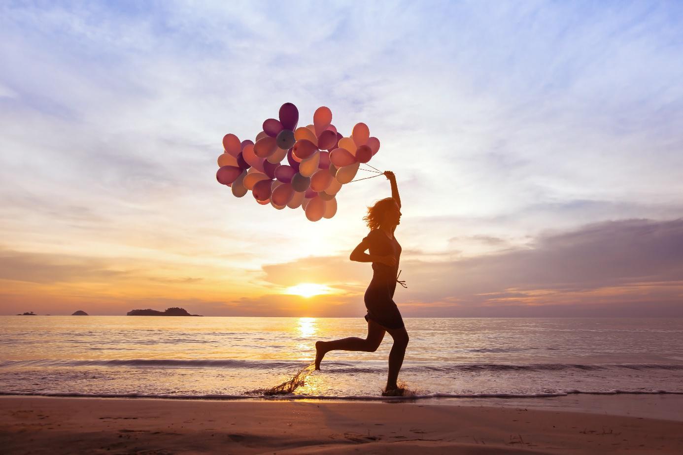 Foto: Frau läuft mit Luftballontraube in Hand vor Sonnenuntergang am Meerufer