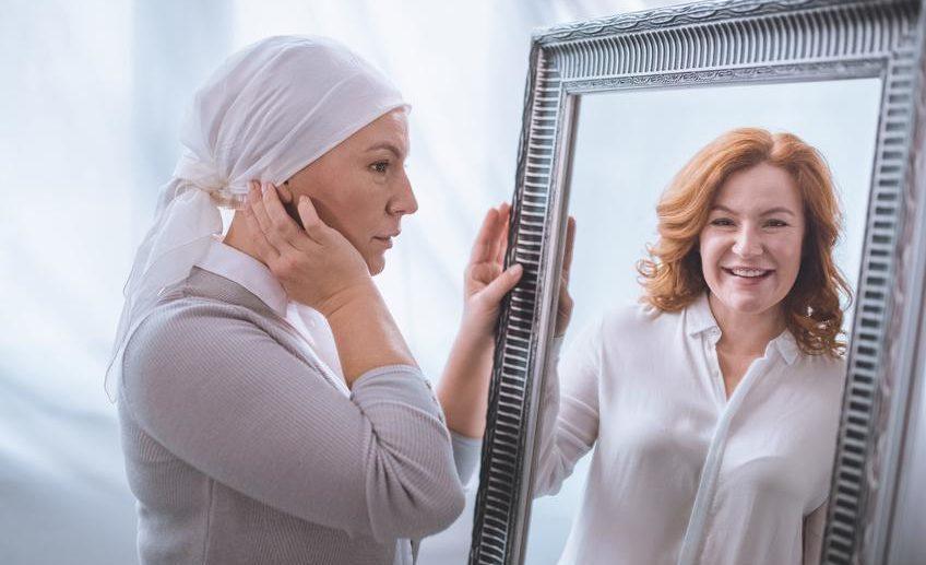 Foto: Frau mit Tuch statt Haaren sieht im Spiegelbild ihr Portrait mit Haaren