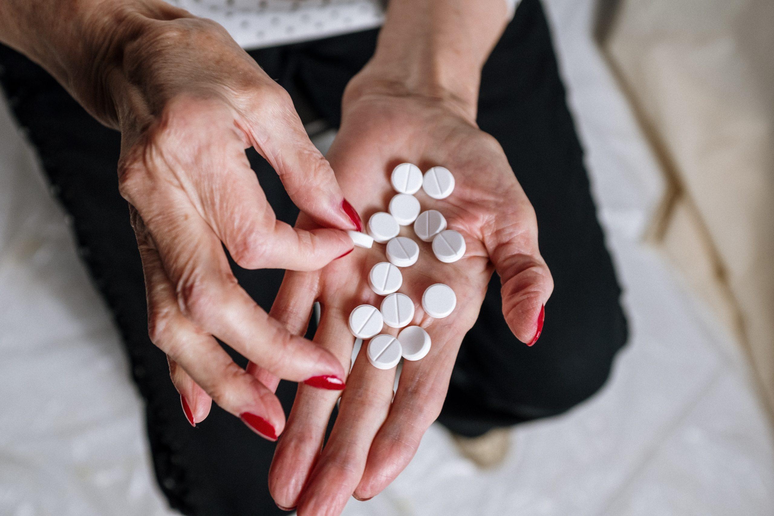 Pillen gegen Alzheimer? Eine ältere Dame hält Medikamente in ihrer linken Hand